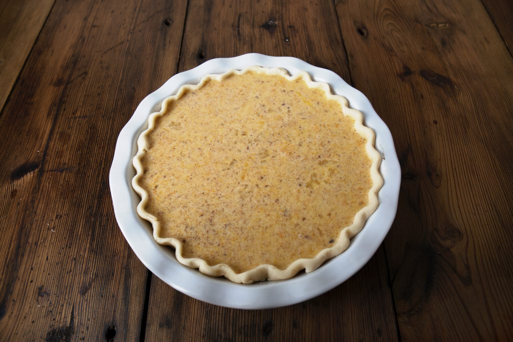 A crimped, raw, pie crust in a pie plate with raw butternut squash pie filling almost to the top of the crust, that sits on a wooden table.