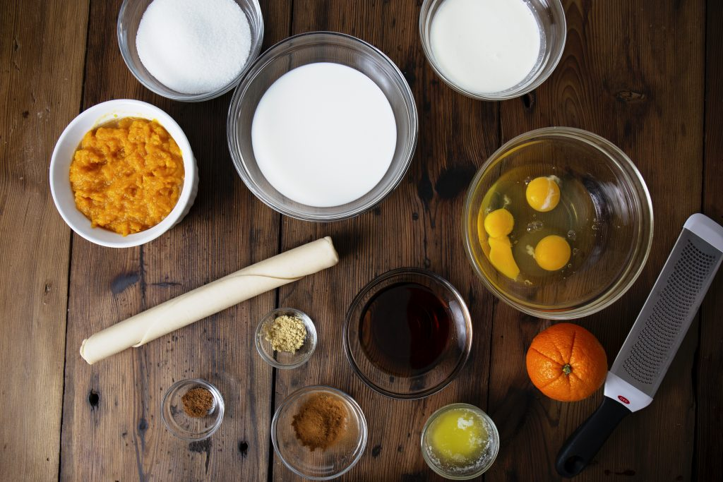 Ingredients for butternut squash pie pictured on a wooden table.