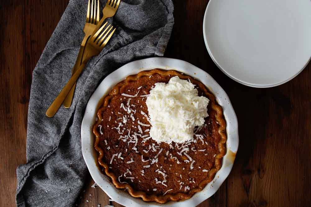 Butternut Squash Pie with forks, plates, and a blue napkin sit on a wooden table. Pie is topped with coconut and whipped cream.