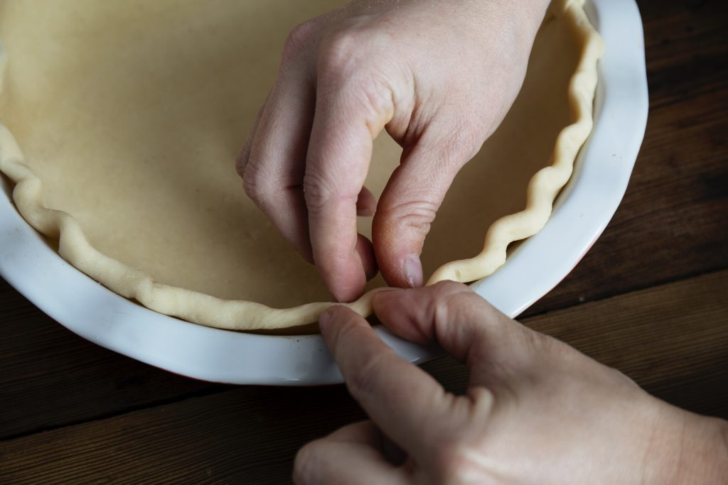 A close-up image of crimping the pie crust with two hands and four fingers in a U shaped fashion.